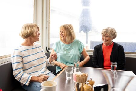 Joyful elderly friends having tea or coffee together. Senior girlfriends chatting laughing and having fun in coffee shop in Stay active in retirement lifestyle and friendship or companionship concept.