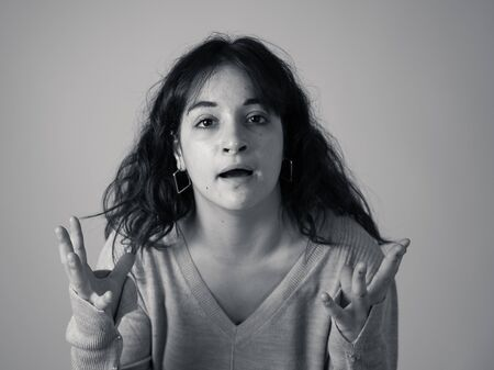 Facial expressions and emotions. Close up portrait of Young attractive hispanic woman with an angry face. Looking mad and crazy shouting and making furious gestures. Isolated on moody background.
