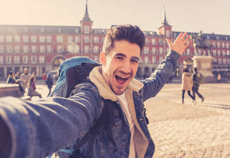 Attractive young tourist student man with backpack having fun excited taking a happy face selfie with smart phone in Plaza Mayor, Madrid, Spain. Vacation, and travel around the world concept. Standard-Bild