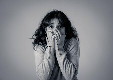 Ciérrese encima del retrato de la mujer joven asustada y conmocionada que recibe malas noticias y que mira con miedo en sus ojos algo aterrador. Concepto de emociones y expresiones humanas y personas. Foto de estudio.