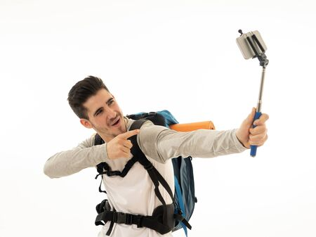 Portrait of young backpacker taking a selfie with his mobile phone isolated on white background. In traveling around the world, staying connected, tourism and social network, living the dream concept.