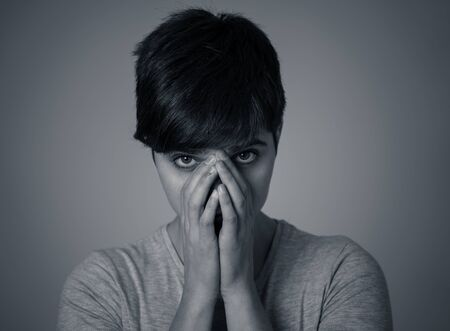Black and white portrait of beautiful young woman looking sad and stressed, her head resting on her hand looking depressed. Human facial expressions and emotions, depression and mental health concept.