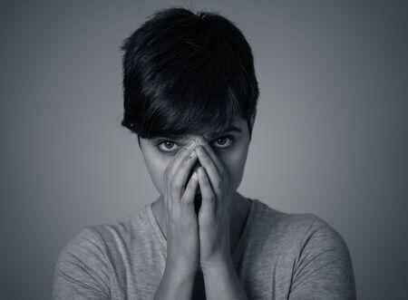 Portrait noir et blanc d'une belle jeune femme semblant triste et stressée, la tête appuyée sur sa main semblant déprimée. Expressions et émotions faciales humaines, dépression et concept de santé mentale. Banque d'images