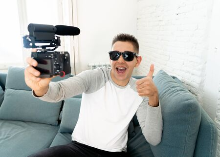 Young cute man in casual clothes style holding camera shooting self portrait photo or recording video in streaming at home. In Social Media Influencer, internet followers and blogger concept.