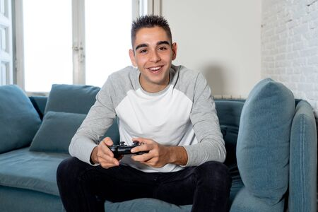 Portrait of young student man playing video games having fun winning the game using wireless remote joystick with freak intense happy face in Male game addiction to console play station and video. Фото со стока