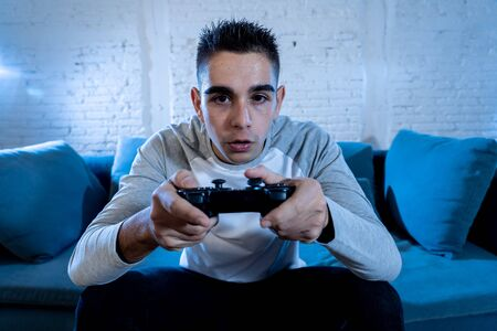 Portrait of young student man playing video games at night using wireless remote joystick with freak intense addicted face having fun in Male game addiction to console play station and video.