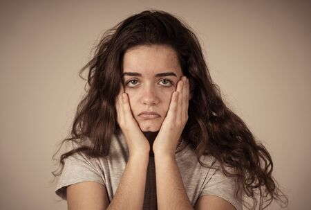 Portrait of beautiful sad miserable young teenager girl with unhappy face feeling emotional pain. Human facial expressions, negative emotions and childhood depression concept. moody background. Stock Photo