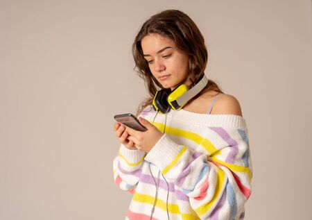 Portrait of gorgeous and cheerful teen woman listening to music in headphones looking for online music on mobile on neutral background. In positive emotions, youth, people, leisure and technology concept.