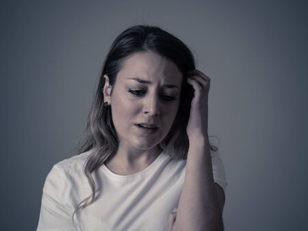 Close up portrait of beautiful young woman with sad mood looking miserable and melancholy. Human facial expressions and emotions, depression and mental health concept. Isolated on neutral background. Banque d'images
