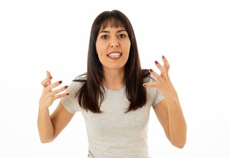 Close up portrait of young attractive caucasian woman with an angry face. Looking mad and crazy shouting and making furious gestures. Isolated on neutral background. Facial expressions and emotions.