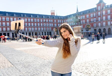Beautiful young woman happy and excited in Plaza Mayor Madrid Spain taking selfie or video with selfie stick posing for her followers, enjoying historical architecture. In tourism, and travel Europe.