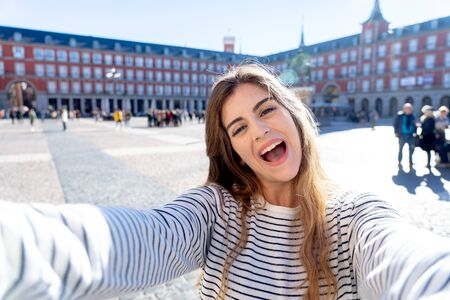 Beautiful student tourist woman happy and excited taking close up selfie in Plaza Mayor Madrid Looking cheerful and joyful having fun. In tourism, travel around europe and posting online adventures. Imagens
