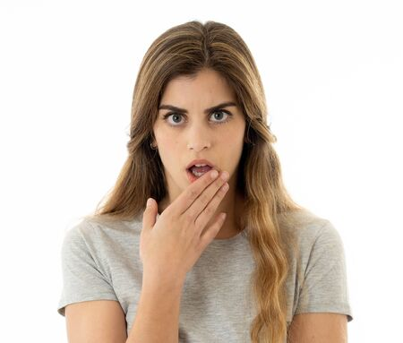 Surprised young woman in her twenties feeling afraid covering mouth in shock reaction, looking with fear in her eyes. People and Human expressions and emotions concept. Portrait Isolated in white.