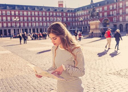 Lost young tourist trying to read a map for finding directions. Looking lost, worried and thoughtful while consulting the city map. In tourism in Europe, Spain, Madrid and technology concept. Stockfoto