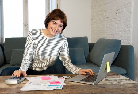 Happy woman with laptop feeling successful accounting home finances calculating costs, charges, mortgage, taxes and paying bills. In e-banking, e-commerce and home or small business accountant.