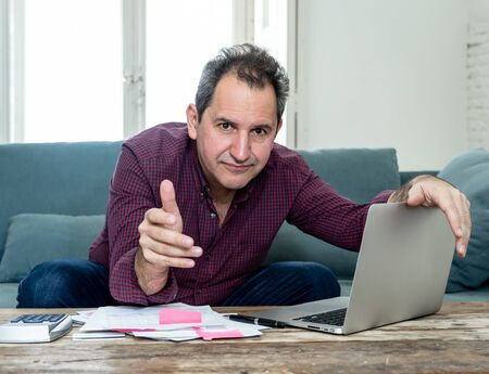 Mature attractive man on computer looking stressed and worried with credit card payments and home finances accounting costs charges taxes and mortgage in paying bills financial problems and debts.