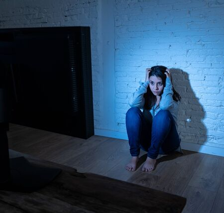 Dramatic portrait of intimidated lonely young woman on ground staring at computer at night suffering harassment and cyberbullying. Abused by online stalker feeling desperate in dangers of Internet.