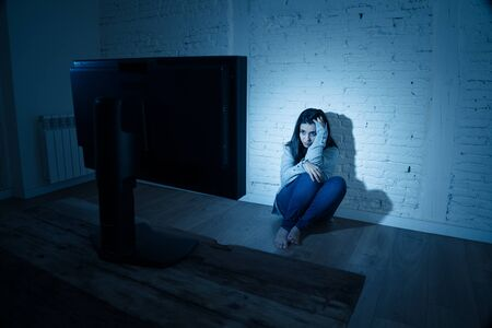 Dramatic portrait of sad scared young woman on the ground staring a computer suffering cyberbullying and harassment. Being online abused by stalker feeling desperate. Dangers of internet concept.