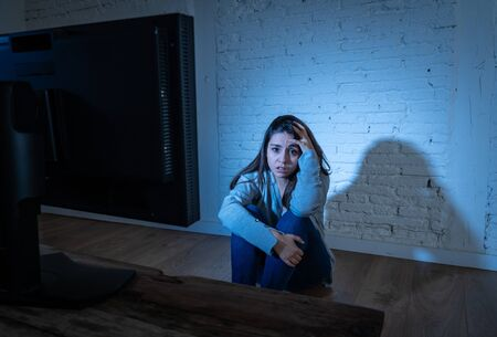 Dramatic portrait of intimidated depressed young woman on ground staring at computer suffering harassment and cyberbullying. Being online abused by stalker feeling desperate. Dangers of in Internet. Banque d'images