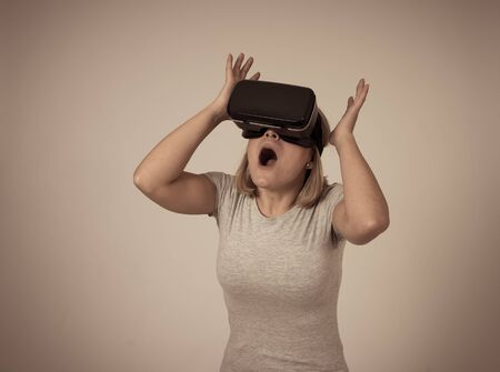 Excited and shocked woman using augmented or virtual reality goggles feeling new experiences during VR simulation , exploring virtual life making gestures to touch 3D world. New technology