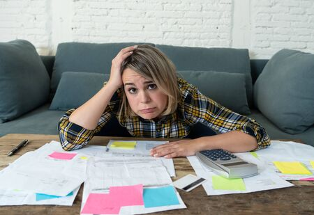 Portrait of worried and desperate young entrepreneur woman accounting home or small business finances feeling stressed not able to pay off debts, bills, rent and expenses. In financial problems.