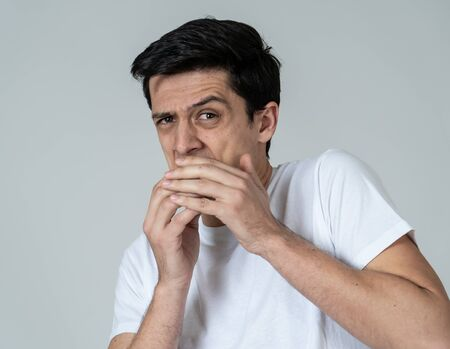 Young man feeling scared and shocked making fear, anxiety gestures. Looking terrified and desperate trying to cover himself. Portrait with copy space. People and Human expressions and emotions.