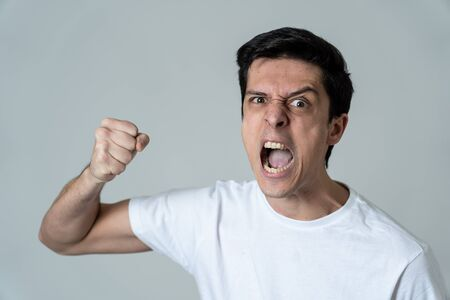Close up of young caucasian male with an angry face. Looking mad, crazy, aggressive with fist clenched in anger. Isolated on white background. Facial expressions and emotions.