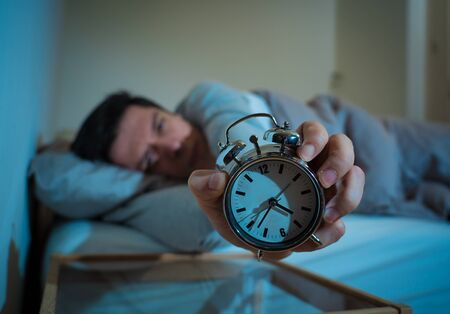 Sleepless and desperate young man awake at night not able to sleep, feeling frustrated and worried looking in distress at clock suffering from insomnia. In mental health, stress and sleep disorder. Banco de Imagens - 127610133