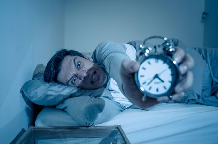 Sleepless and desperate young man awake at night not able to sleep, feeling frustrated and worried looking in distress at clock suffering from insomnia. In mental health, stress and sleep disorder. Banco de Imagens - 127610135