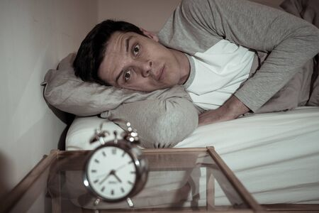 Sleepless and desperate young caucasian man awake at night not able to sleep, feeling frustrated and worried looking at clock suffering from insomnia in stress and sleep disorder concept. Banco de Imagens - 127610139