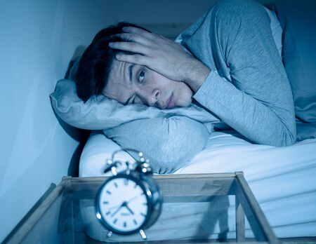 Sleepless and desperate young man awake at night not able to sleep, feeling frustrated and worried looking in distress at clock suffering from insomnia. In mental health, stress and sleep disorder. Banco de Imagens - 127610141