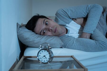Sleepless and desperate young caucasian man awake at night not able to sleep, feeling frustrated and worried looking at clock suffering from insomnia in stress and sleep disorder concept. Banco de Imagens - 127610148
