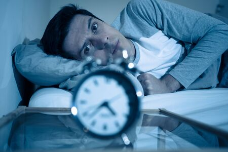 Sleepless and desperate young caucasian man awake at night not able to sleep, feeling frustrated and worried looking at clock suffering from insomnia in stress and sleep disorder concept. Banco de Imagens - 127610177
