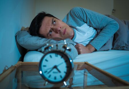 Sleepless and desperate young caucasian man awake at night not able to sleep, feeling frustrated and worried looking at clock suffering from insomnia in stress and sleep disorder concept. Banco de Imagens - 127610180