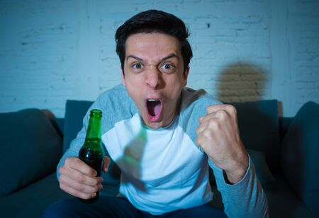Lifestyle portrait of football fan young man with beer watching soccer football game on TV late at night. Screaming and celebrating goal or victory. In sports, people, entertainment and celebration. Standard-Bild