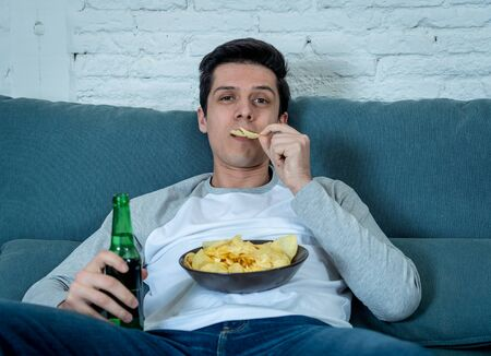 Lifestyle portrait of young bored man on couch with remote control zapping for movie or live sport. Looking disinterested drinking beer. Sedentary and mass social media or Television addiction.