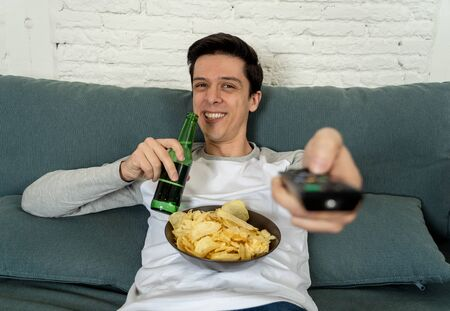 Lifestyle portrait of young man on sofa watching sports or exciting movie on television. Having fun at home enjoying and celebrating goal and victory drinking beer. In entertainment and mass media. 免版税图像