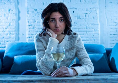 Portrait of depressed woman drinking glass of wine alone at home. Feeling distress, hopeless and frustrated, trying to feel better drinking. Unhealthy behavior, depression and alcohol concept.