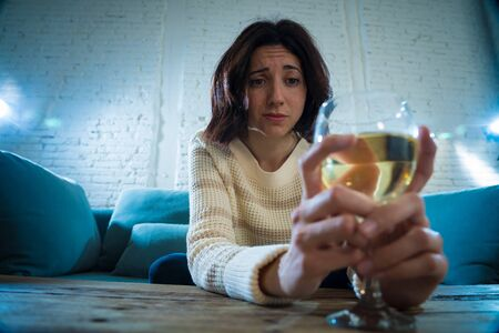 Portrait of depressed woman drinking glass of wine alone at home. Feeling distress, hopeless and frustrated, trying to feel better drinking. Unhealthy behavior, depression and alcohol concept. Imagens - 127777969