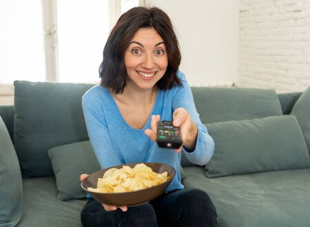 Happy woman on sofa with TV remote control zapping for another movie or favorite TV Show. Looking enthusiastic, making gestures of approval and eating chips. In people, technology and leisure concept. Stock Photo