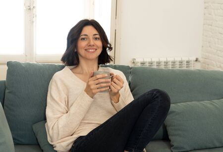 Lifestyle portrait of young pretty relaxed woman drinking hot coffee or chocolate feeling happy and cozy at home smiling happy on the couch. In leisure, peaceful life, happiness lifestyle concept.