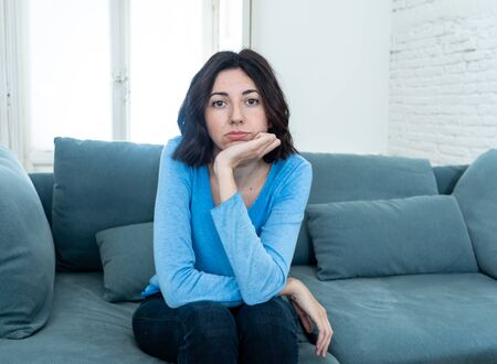Young upset woman on sofa using control remote zapping bored of bad TV shows and programing . Looking disinterested, aloof and sleepless. People, too much bad television and Sedentary lifestyle.