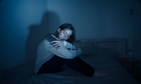 Young teenager girl suffering mobile cell phone addiction feeling lonely and depressed having insomnia needing to be connected sitting on bed late at night. In