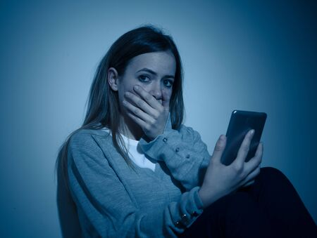 Sad desperate young teenager female girl on smart phone suffering from online bulling and harassment felling lonely and hopeless sitting on bed at night. CYberbullying and dangers of internet concept. Stock Photo - 127853275