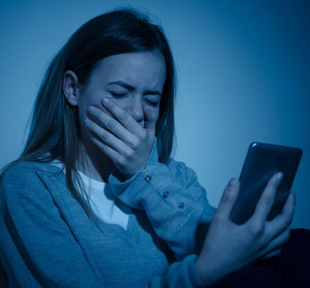 Sad desperate young teenager female girl on smart phone suffering from online bulling and harassment felling lonely and hopeless sitting on bed at night. CYberbullying and dangers of internet concept.