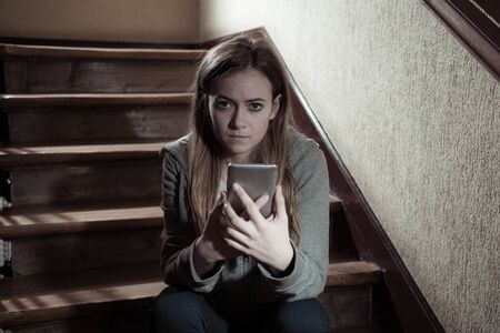 Teenager girl victim of online stalker suffering from cyberbullying abuse feeling lonely and hopeless sitting on stairs with dark light. Dangers of internet, online grooming and harassment concept. Stock Photo - 127853091