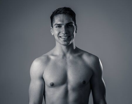 Strong handsome Athletic young man isolated on neutral background. Mixed race latin muscly model posing for fitness marketing advertising. In exercise, healthy lifestyle, workout and body care.
