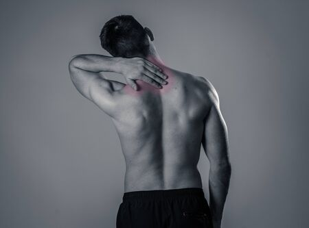 Young muscular fit man touching and grabbing neck and upper back suffering cervical pain after workout. Isolated on neutral background. In sport injury Incorrect posture problems and body health care.