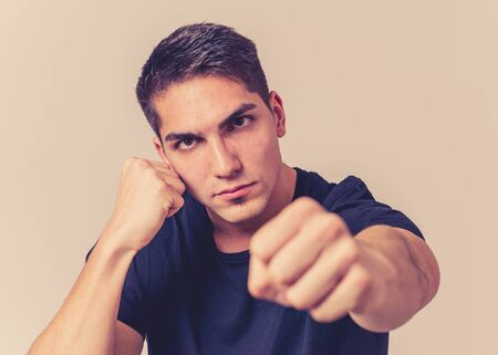 Close up portrait of an attractive young man with angry face looking furious in defence stance having an argument or fight. Isolated on neutral background. In People, boxing and negative emotions.