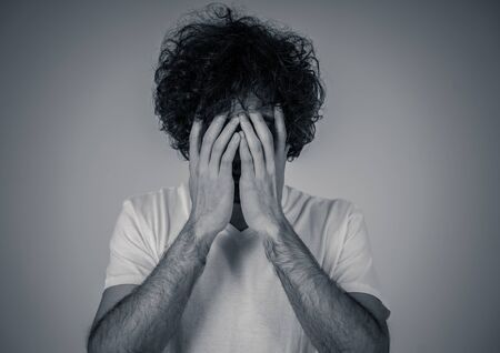 Portrait of young sad man, worried and concerned, looking depressed and desperate. Feeling sorrow and fear. With white copy space. In People, facial expressions and emotions and mental health concept.